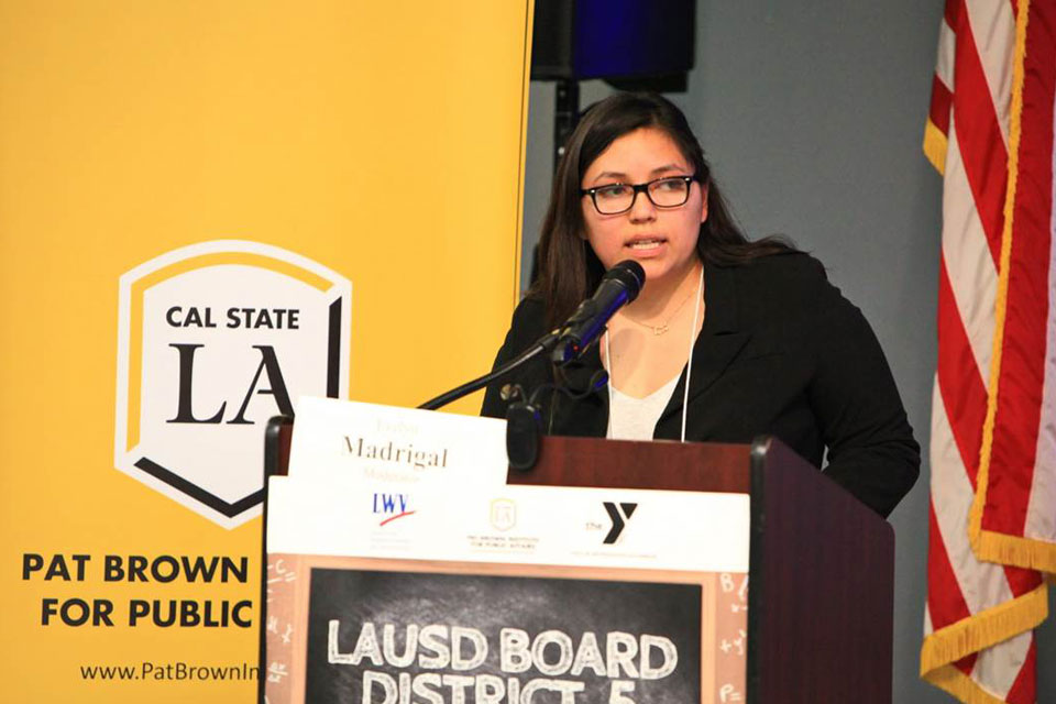 Evelyn Madrigal speaks from behind a podium.