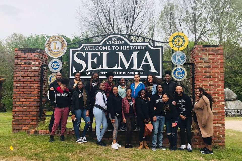 The students and faculty and staff chaperones at the welcome sign in the city of Selma.
