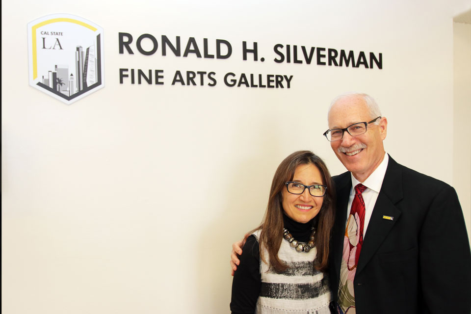 Cal State LA alumni Amelia Perez-Silverman and Jeffrey Silverman in front of the sign for the newly named Ronald H. Silverman Fine Arts Gallery.