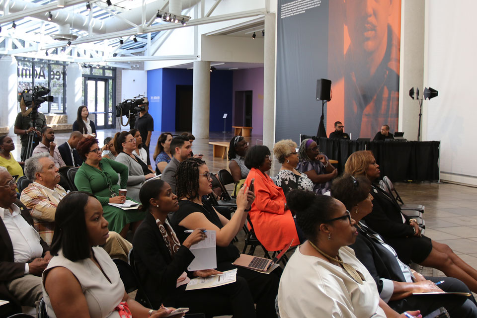 A crowd inside the California African American Museum listens to the poll presentation.