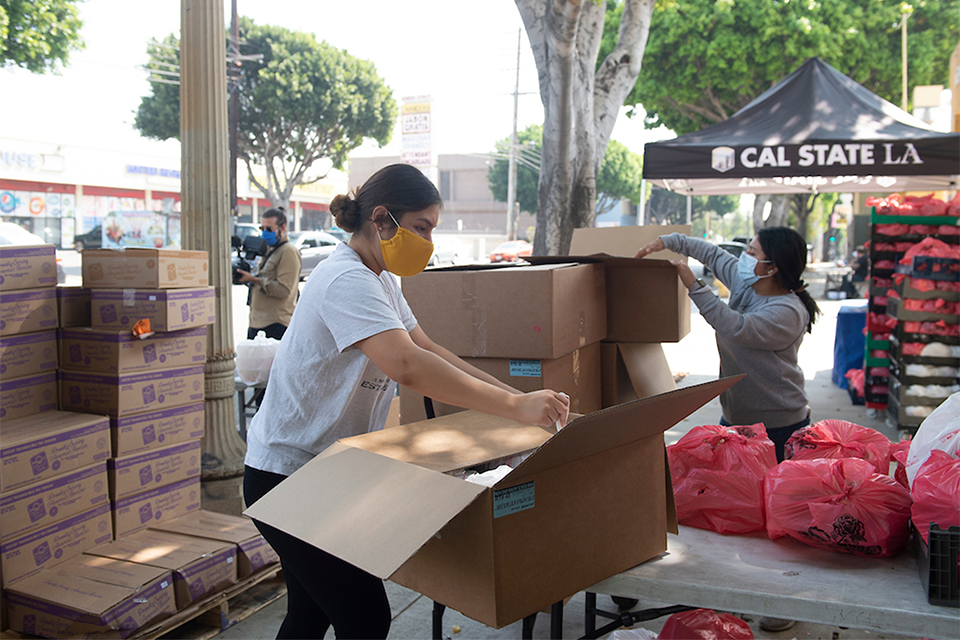 A woman wearing a mask assembles a box of food for distribution.
