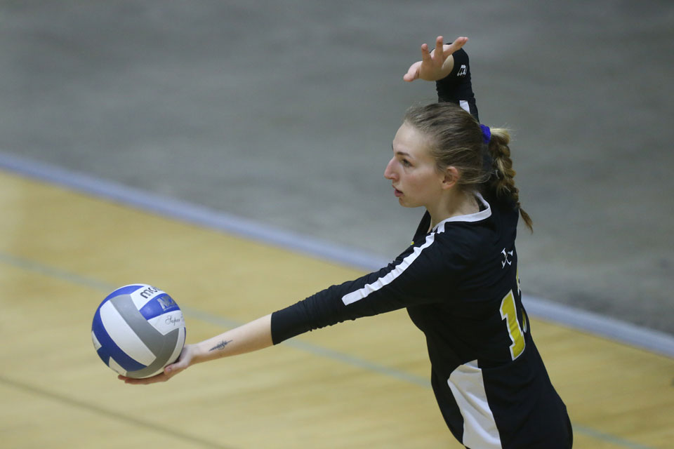 Shelby Grubbs serving a volleyball.