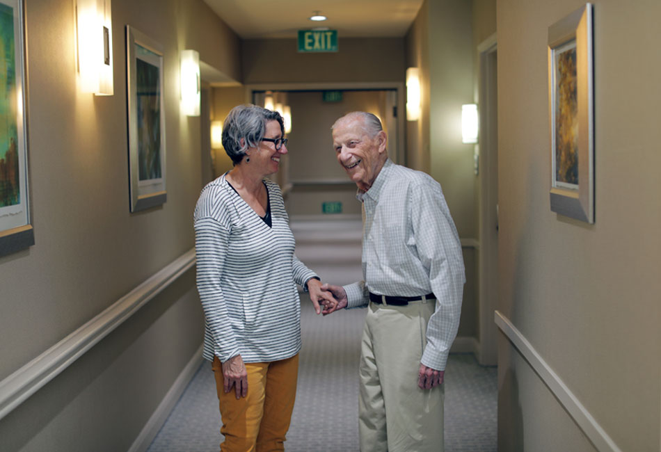 Sigmund Burke and his daughter Robin Berkovitz laughing and holding each other's hands.