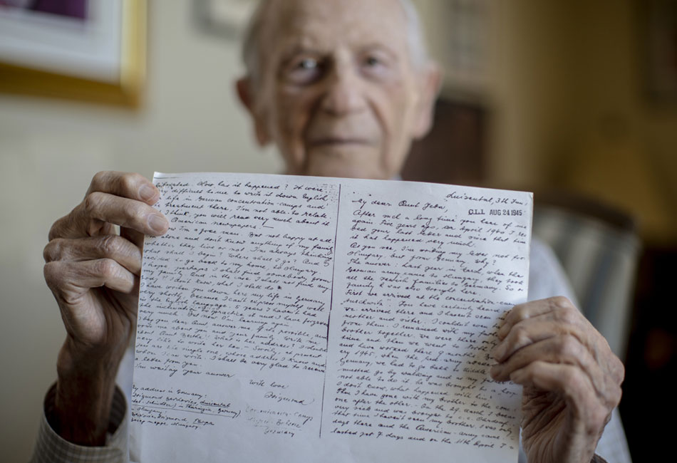 Sigmund Burke holds a handwritten letter he wrote to family in the United States in August 1945. Letter is in focus, Burke is blurred in background.