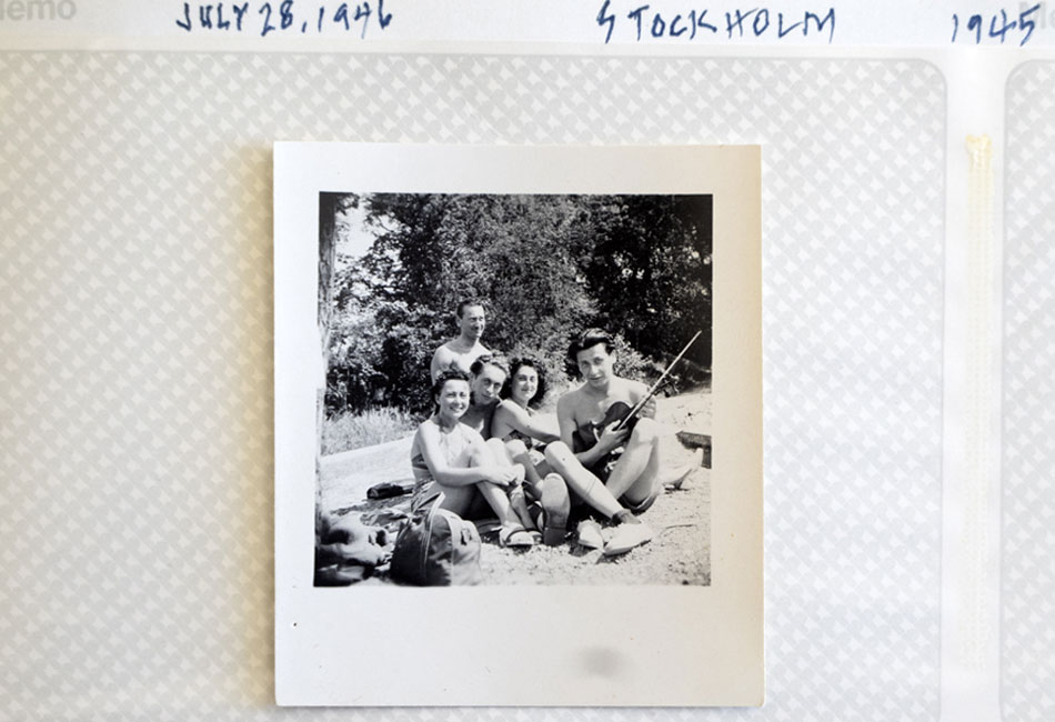 Black-and-white Polaroid photo showing five friends, one holding a violin.