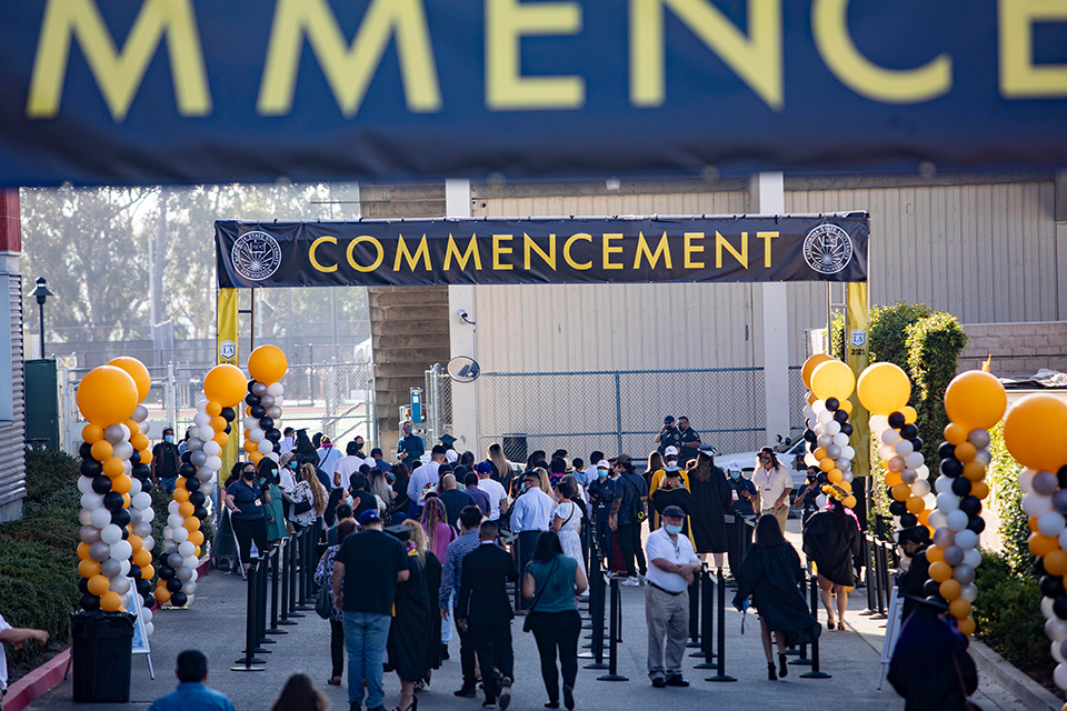 Guests and graduates file into the Commencement area under a black and gold Commencement banner.