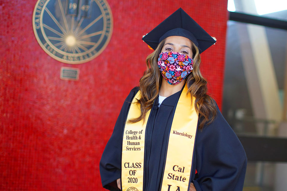 Graduate, Victoria Florez, posing for a photo in front of the Cal State LA administration building.