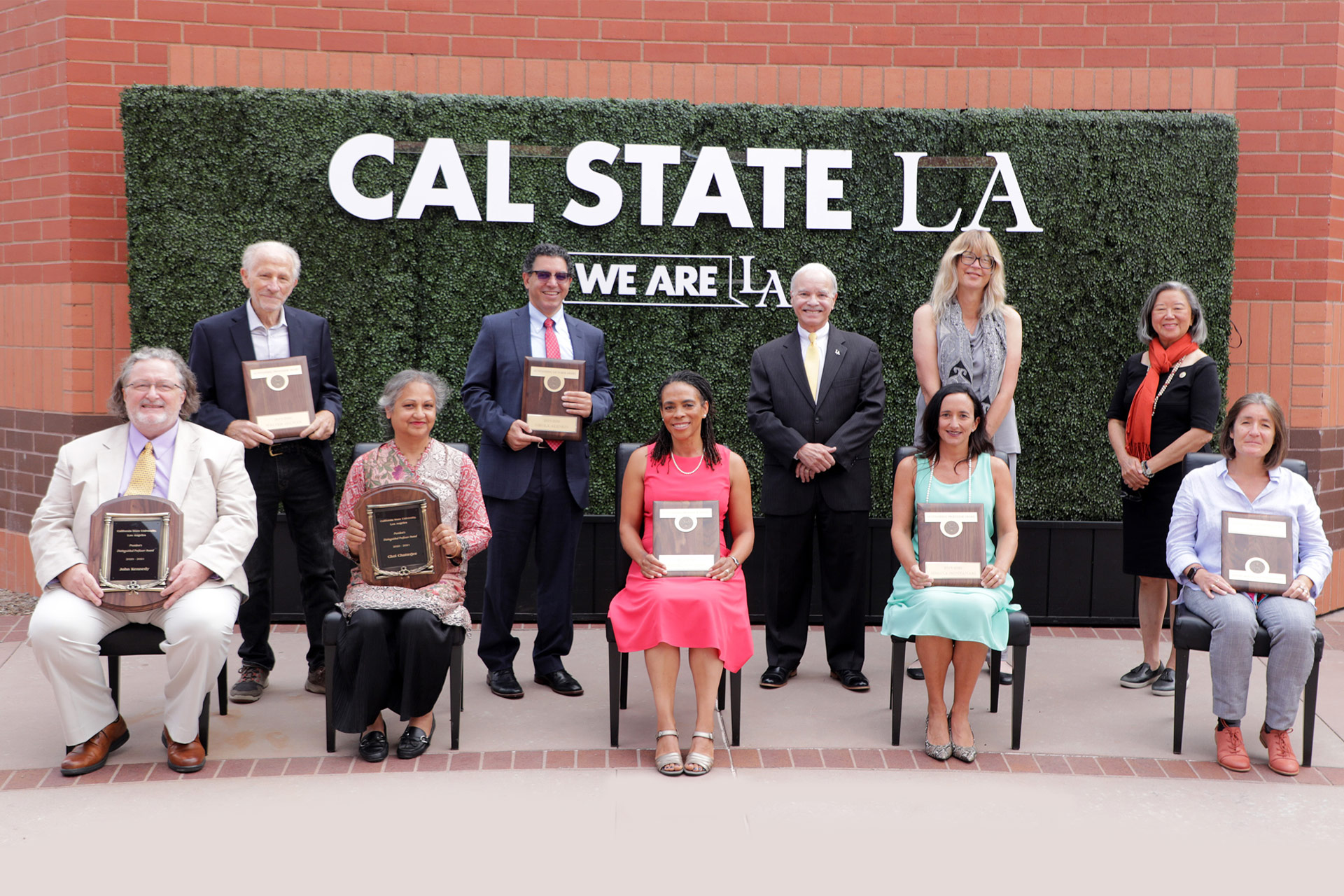 Ten faculty and administrators standing in front of decorative hedge that says Cal State LA, We Are LA